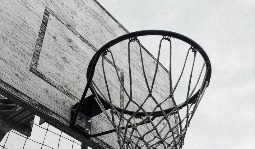 A dim photo of a basketball ring which reveals uncertainty regarding sports in times of the pandemic.