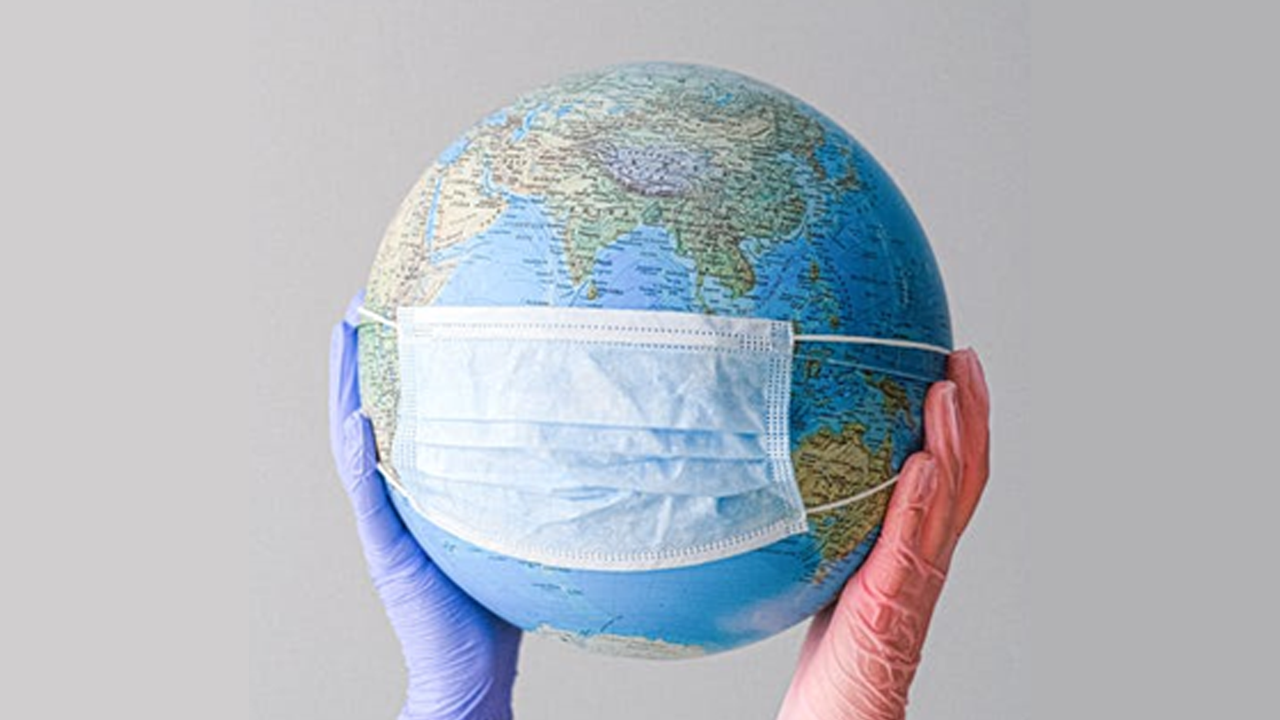 A picture of two gloved hands holding an earth with a surgical face mask on.